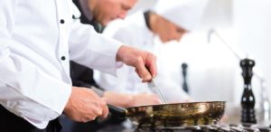 Three chefs - men and woman - in hotel or restaurant kitchen working and cooking in team