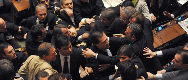Officials of the Parliament try to stop deputies fighting after a member of the Futura e Liberta (FLI) group decided to give her voice to Italian Prime Minister Silvio Berlusconi during a confidence vote at the Chamber of Deputies, the Italian lower house, on December 14, 2010 in Rome. Italy held its breath as lawmakers staged a knife-edge confidence vote on Prime Minister Silvio Berlusconi's government that could bring down the flamboyant Italian leader. AFP PHOTO / ANDREAS SOLARO (Photo credit should read ANDREAS SOLARO/AFP/Getty Images)